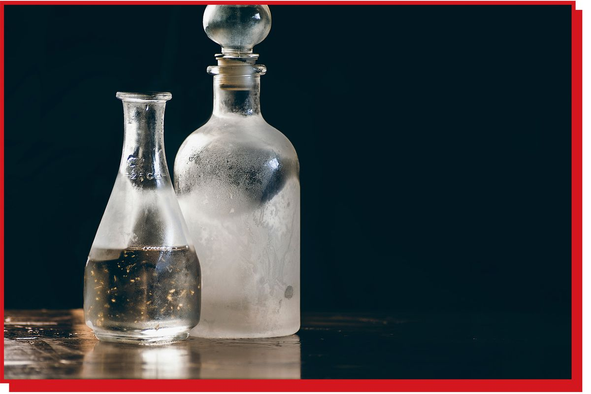 Frosted glass decanter contains a clear liquid, it sits next to a clear open bottle containing clear liquid.