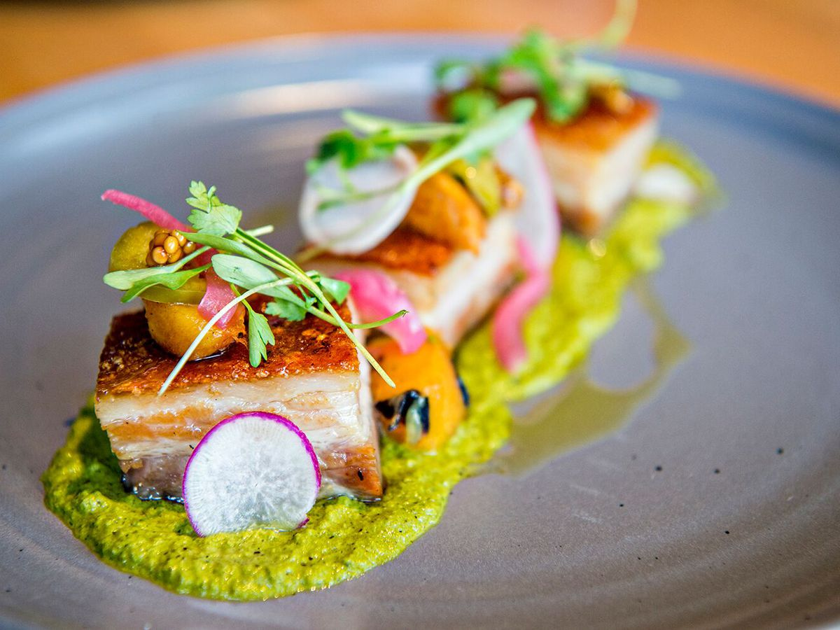 A photo of three pieces of pork belly from American Elm on a plate