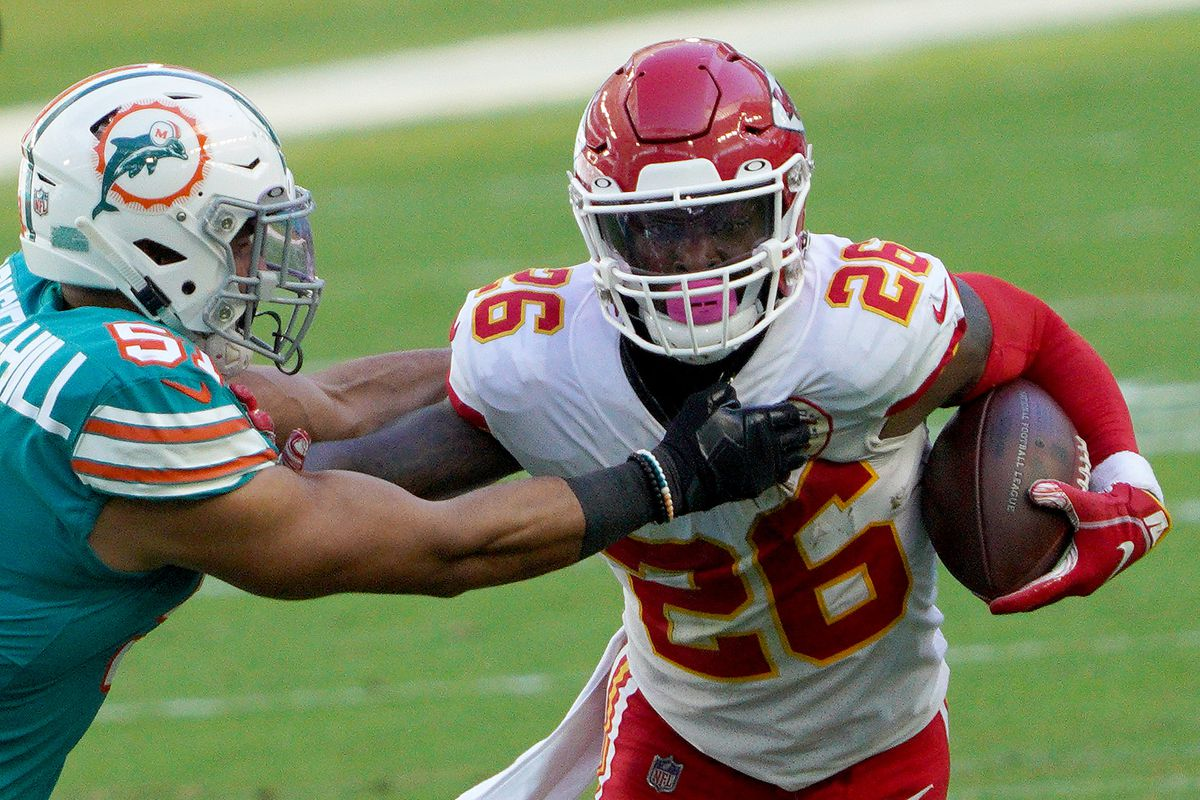 Le'Veon Bell #26 of the Kansas City Chiefs carries the ball against Kamu Grugier-Hill #51 of the Miami Dolphins during the first half of the game at Hard Rock Stadium on December 13, 2020 in Miami Gardens, Florida.