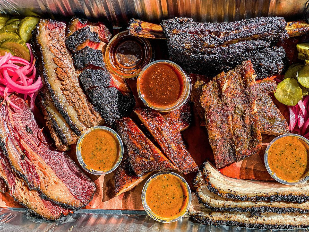A close up of a tray of Texas-style barbecue including pink pastrami, brisket, and more.