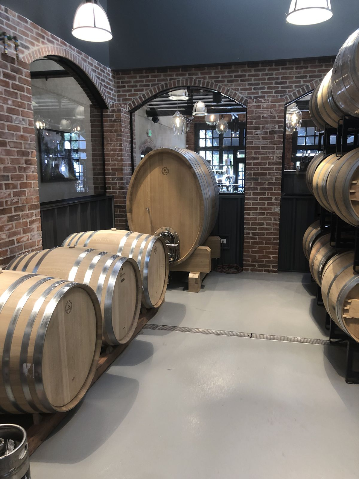 A photo of the barrel room at Carboy, which contains several barrels including a very large one in the corner