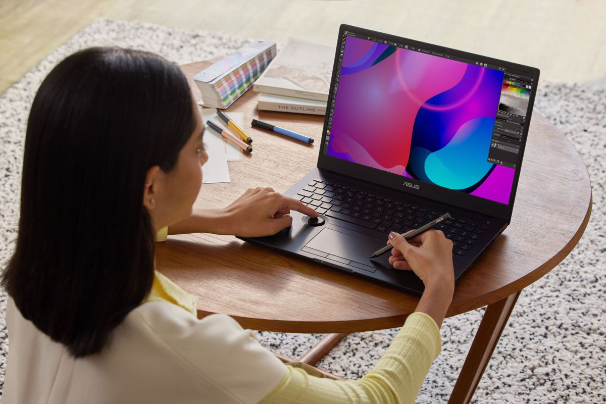 A user uses the ProArt Studiobook 16 OLED, drawing on the touchpad with a stylus and operating the Asus Dial. The laptop sits on a small circular table with scattered pens to its left.