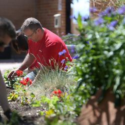 Key Bank employees, including Ryan VanLeeuwen, work in the GEM Court Garden of the George E. Wahlen Department of Veterans Affairs Medical Center at Key Bank's national Neighbors Make The Difference Day in Salt Lake City on Wednesday, May 14, 2014. Nearly 7,000 bank employees, across the country and in Utah, will spend the afternoon volunteering for a wide array of community service projects.