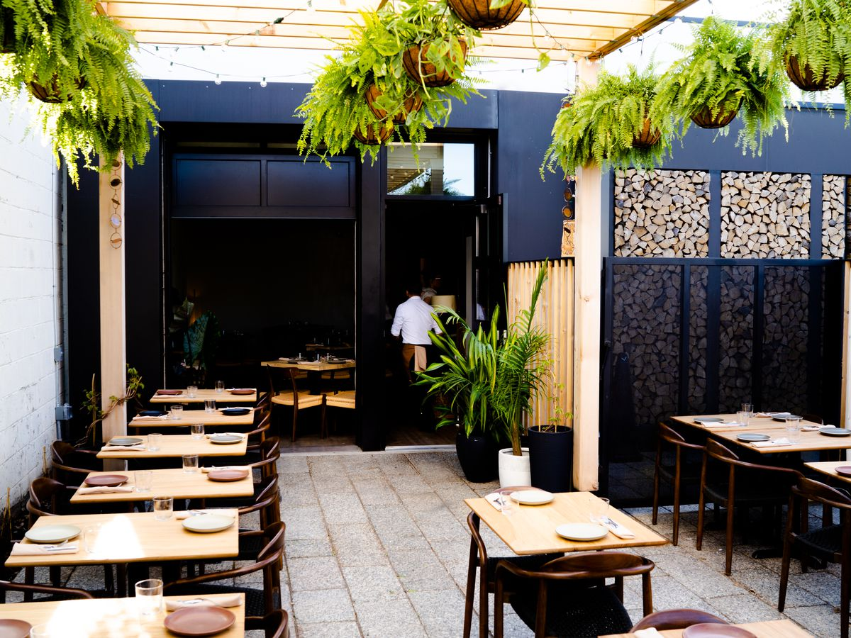 The black exterior and light filled patio outside Colita has a stack of chopped wood in the background and is decorated by hanging ferns.