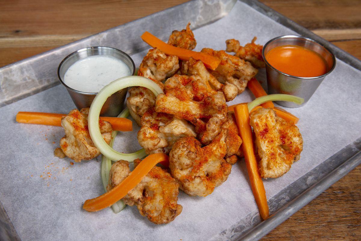 A sheet pan full of fried cauliflower with orange seasoning and metal ramekins full of sauces.