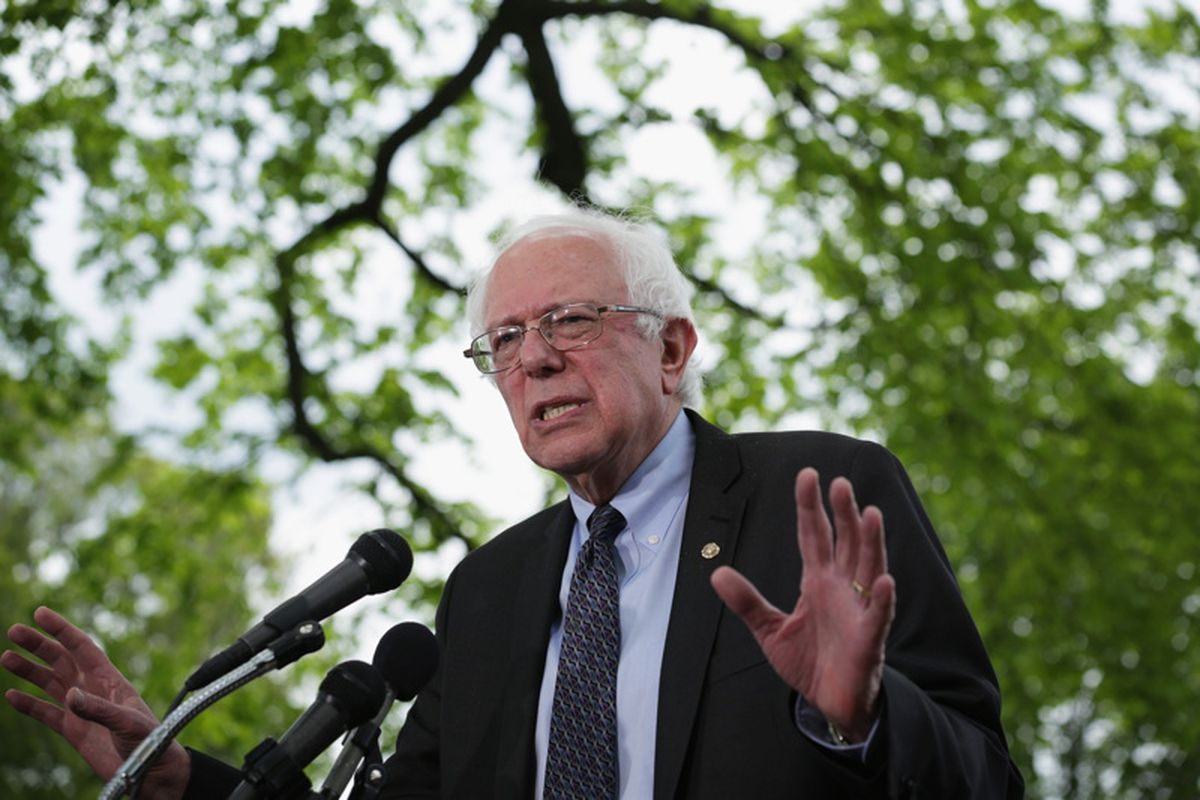 Senator Bernie Sanders speaking at a podium microphone with trees in the background.
