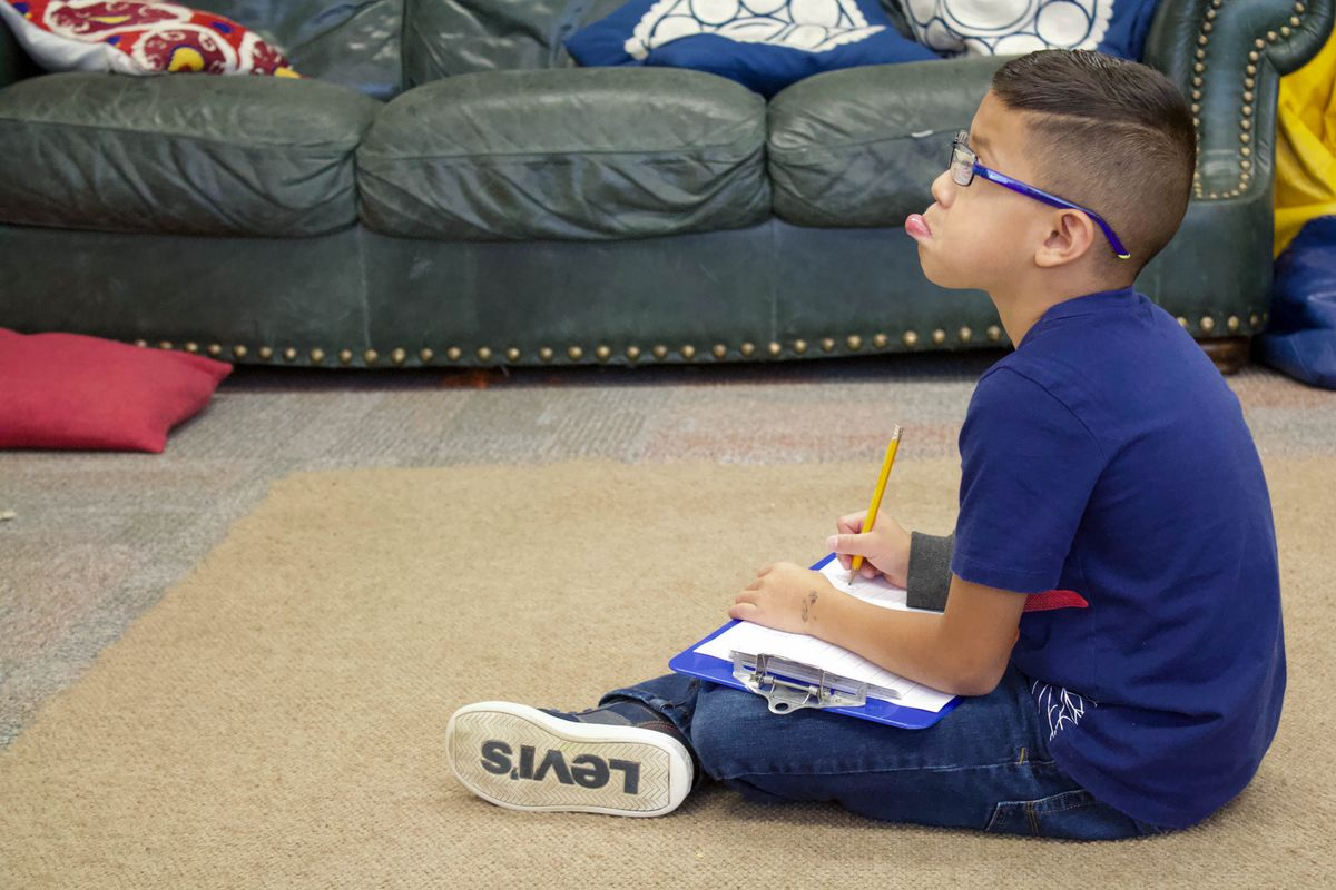 A Lake County elementary school student works on an assignment away from his desk. (Photo by Nic Garcia/Chalkbeat)