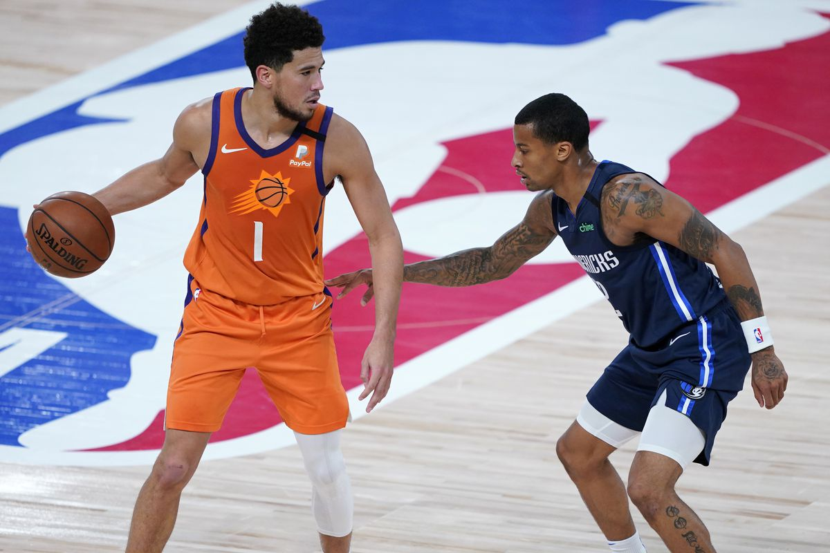 Devin Booker #1 of the Phoenix Suns controls the ball against Trey Burke #32 of the Dallas Mavericks in the second half at AdventHealth Arena at ESPN Wide World Of Sports Complex on August 13, 2020 in Lake Buena Vista, Florida.