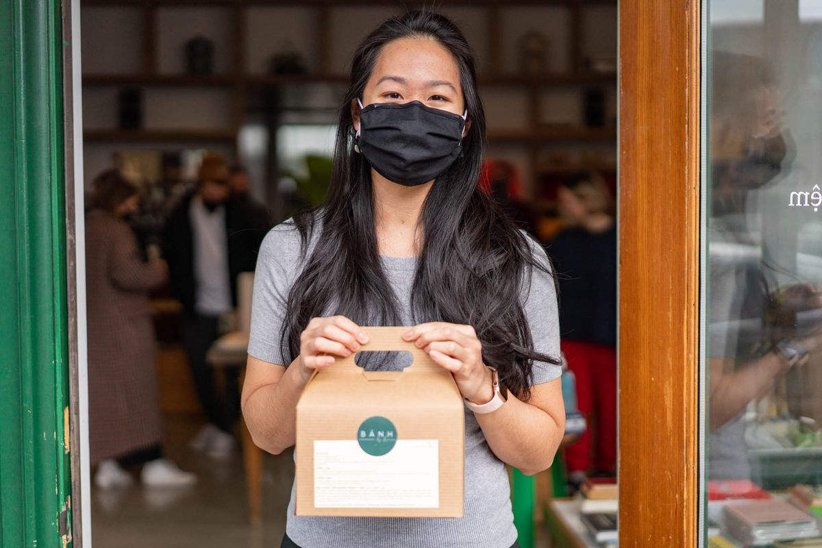 A woman with long black hair and a black face mask on stands in front of a shop holding a brown box filled with pastries