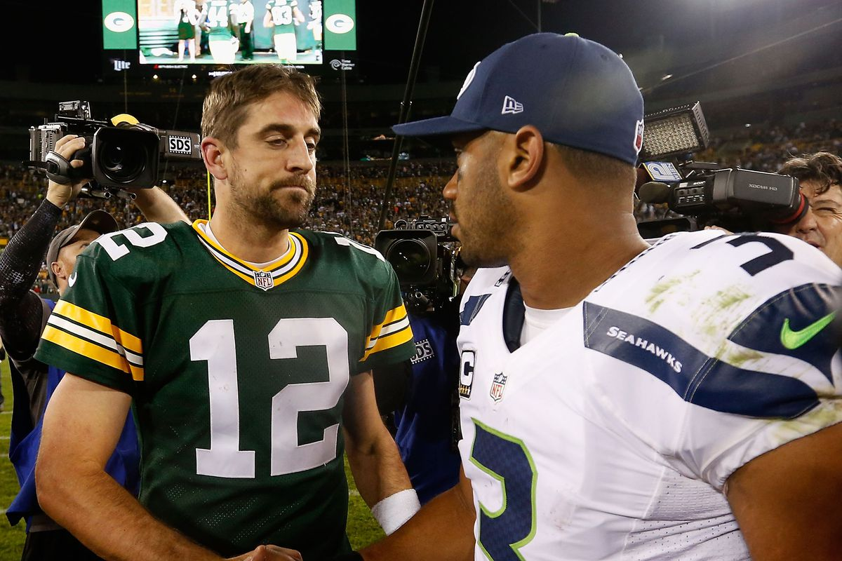 Quarterbacks Aaron Rodgers of the Green Bay Packers and Russell Wilson of the Seattle Seahawks shake hands following the NFL game at Lambeau Field on September 20, 2015 in Green Bay, Wisconsin.