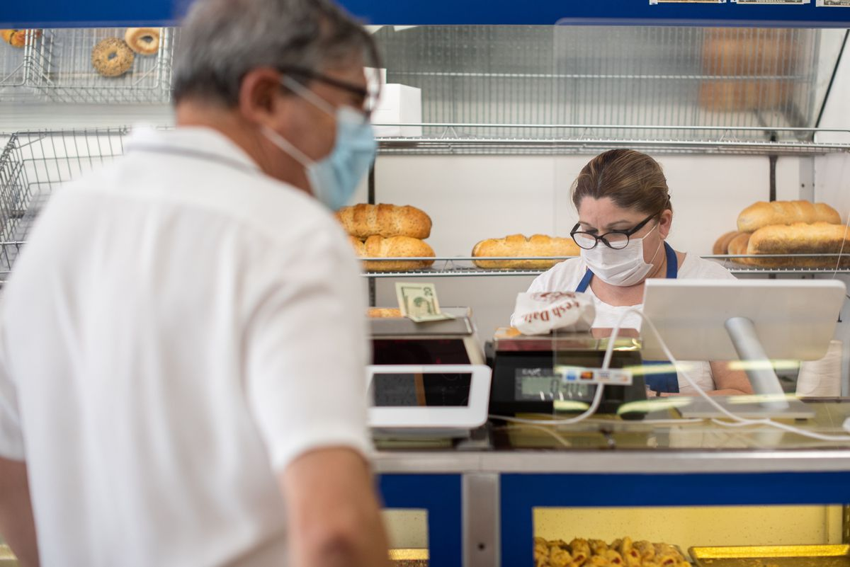 An employee in glasses helps out a customer at an aging bakery.