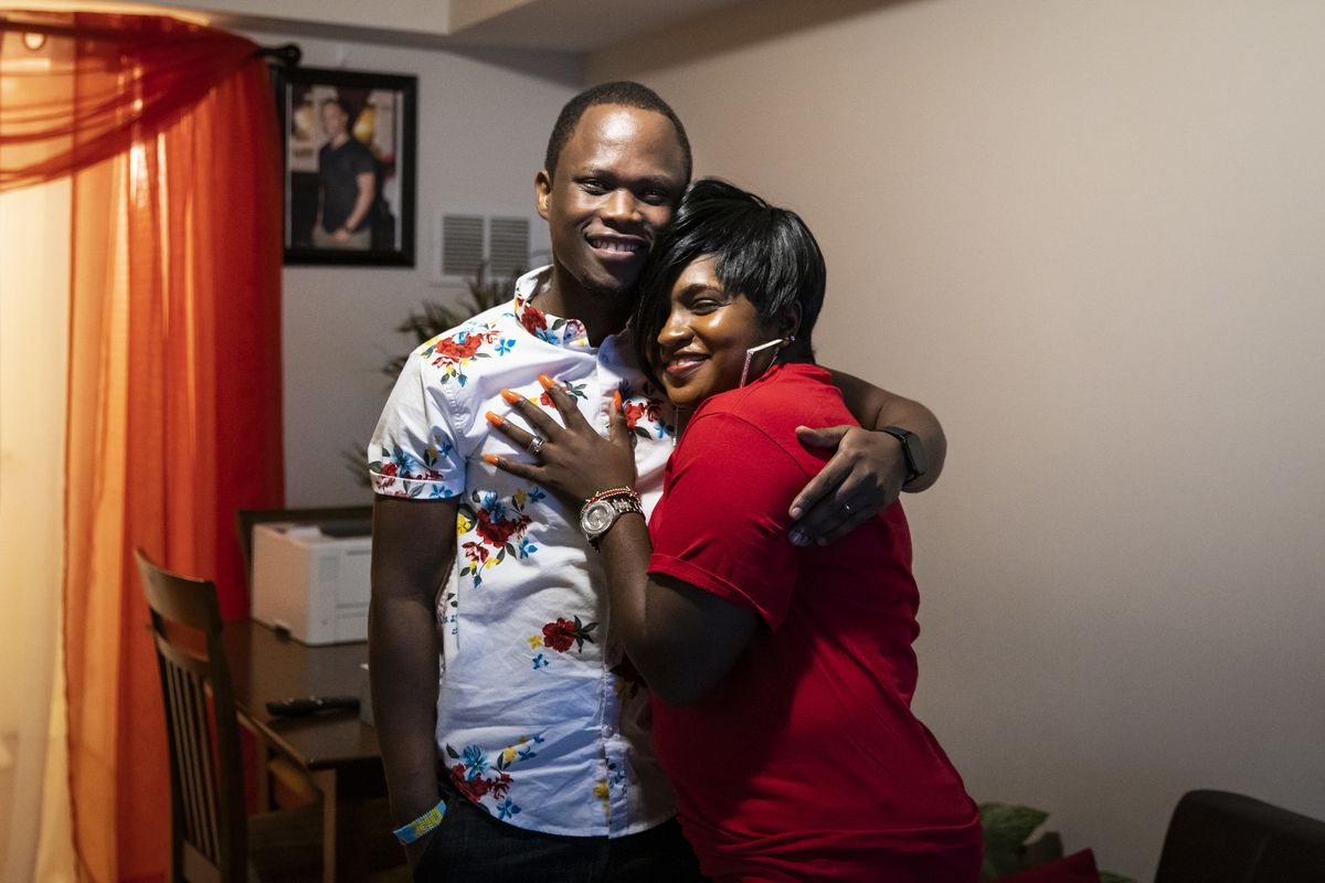 Celestine Mugisha and his wife, Winniefred Akello, pose for a photo in their apartment in Rogers Park on the North Side, Dec. 21, 2020. Mugisha and Akello were married in Uganda in September 2016 and, days later, Mugisha moved to Chicago as part of the United States' refugee resettlement program. More than three years later, Akello was also resettled through the program and the couple was reunited at O'Hare International Airport on Jan. 22, 2020.