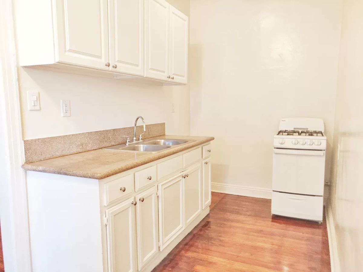 Kitchen with white cabinets and a small stove on the right.