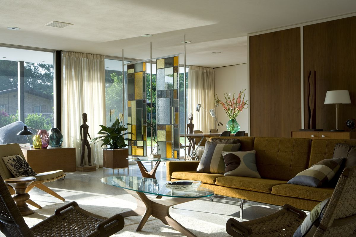 Interior shot of open-plan living room with walls of glass, stained-glass divider, paneled walls and period furniture.