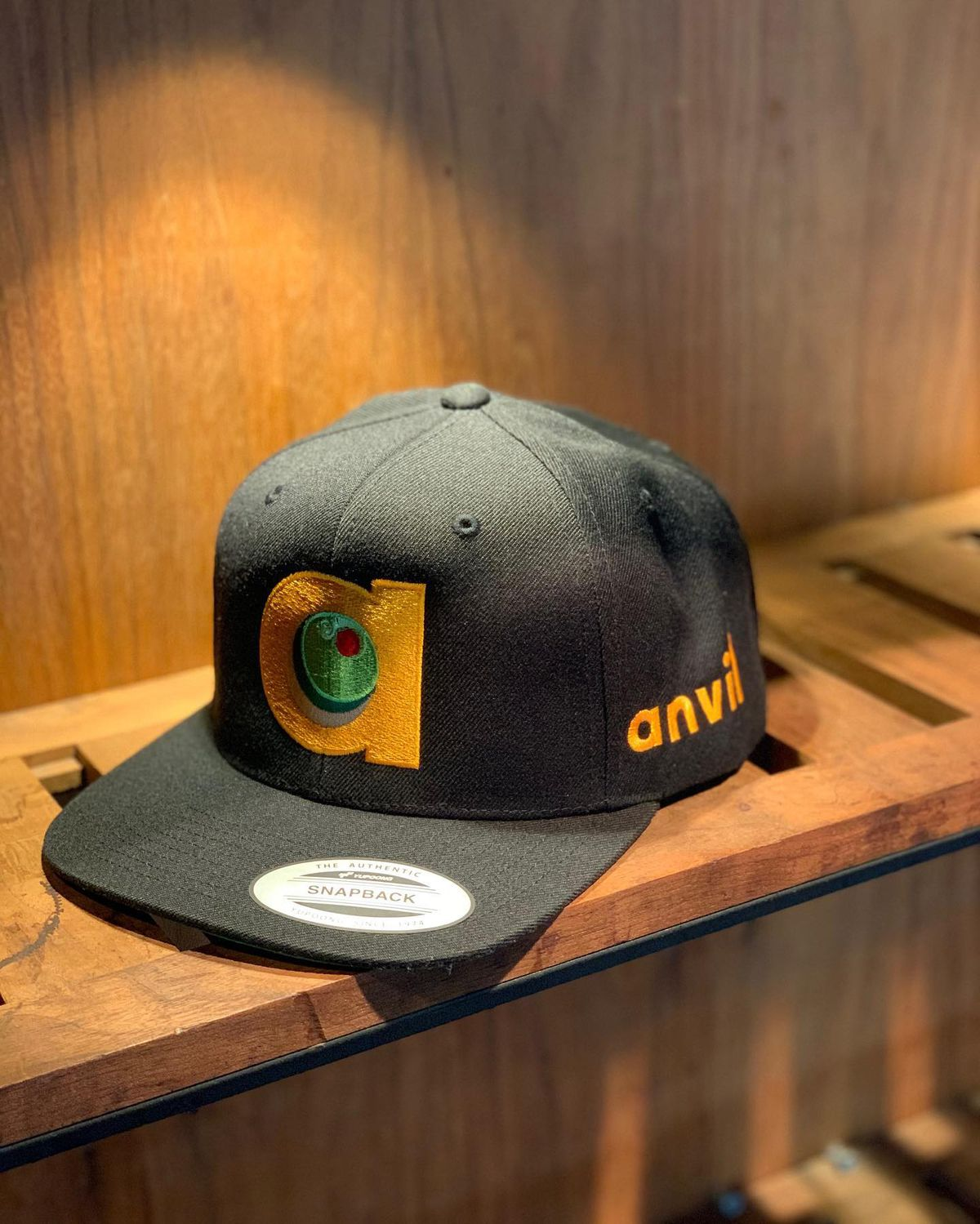 """A black hat with an embroidered lower case """"a."""" An olive is in the middle of the A, and """"anvil"""" is written in lower-case letters on the right side of the hat."""