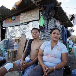 Allan and Jennifer Dela Cruz sit in Tacloban, Tuesday, Nov. 19, 2013. Behind them is a sign asking for help in finding family members they lost in a typhoon.