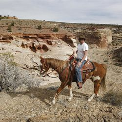 Dave Bennion rides along the cliff while riding horses in the Sid's Mountain Wilderness Study Area of the San Rafael Swell  Friday, April 1, 2011, in the San Rafael Swell in Central Utah.