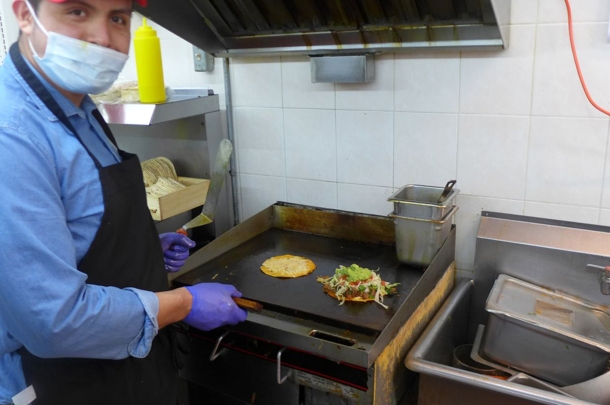 A man with a mask faces us as he works on a mulita on a small blackened griddle.