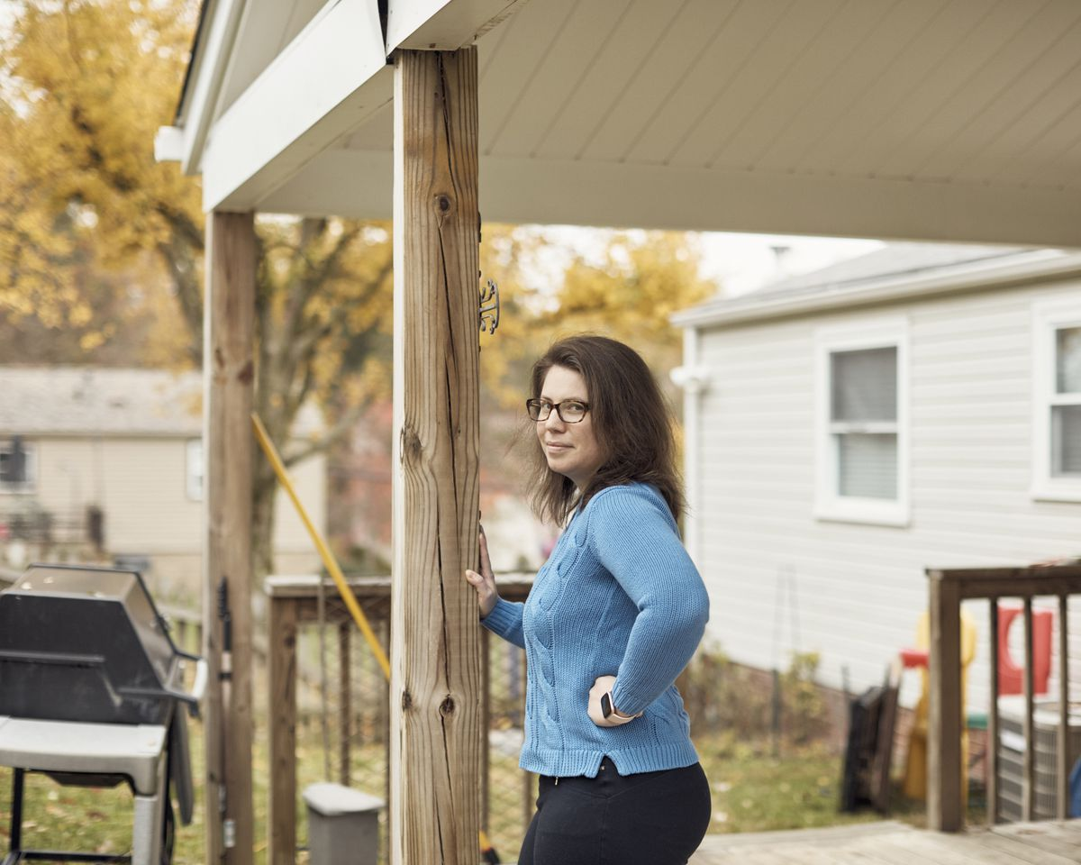 Mazzocco leans against a wooden beam on the front porch of a house; she has dark brown hair and black glasses, and is in a baby blue sweater. The leaves on a tree behind her are yellow, and behind her, the grey vinyl siding of her house can also be seen.