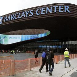 Pedestrians pass the main entrance to the Barclays Arena in New York, Thursday, Sept. 20, 2012 as workmen complete their cleanup for Friday's ribbon-cutting ceremony.  A new chapter in Brooklyn's history Friday when the Brooklyn Nets new arena will open, just across the street from the spot where the Dodgers owner once tried to build a baseball stadium that never saw the light of day.