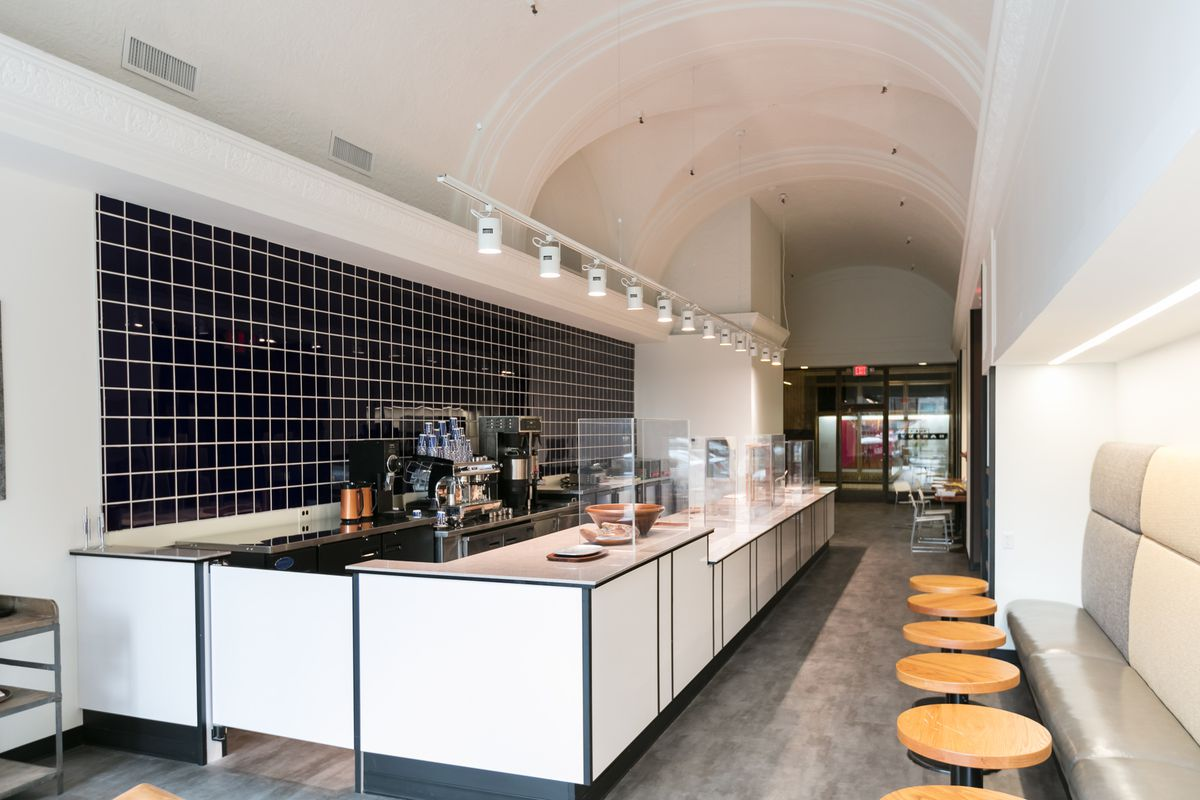 A narrow, white cafe with curved ceilings and a counter with a blue tile backsplash.