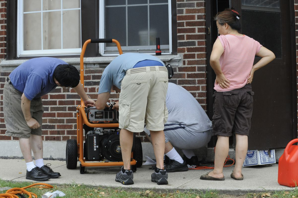 A group of four people are setting up a portable generator after a storm hit the Chicago area in July 2011.
