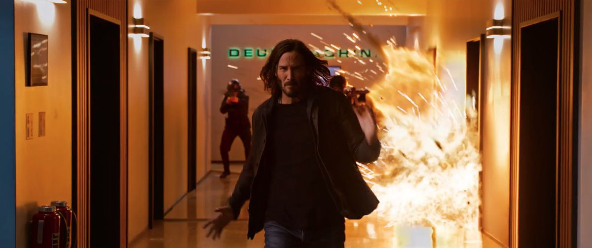 Keanu Reeves' Neo runs away from a blast in The Matrix Resurrections