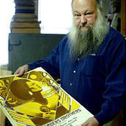 Ken Sanders holds up a 1974 Chambers Brothers concert poster.