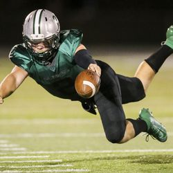 Olympus quarterback Frankie Goodson (2) dives for a first down after being tripped up near the sideline during the second half of a high school football game against Kearns at Olympus High School in Holladay on Friday, Aug. 30, 2019. Kearns won the game 26-21.