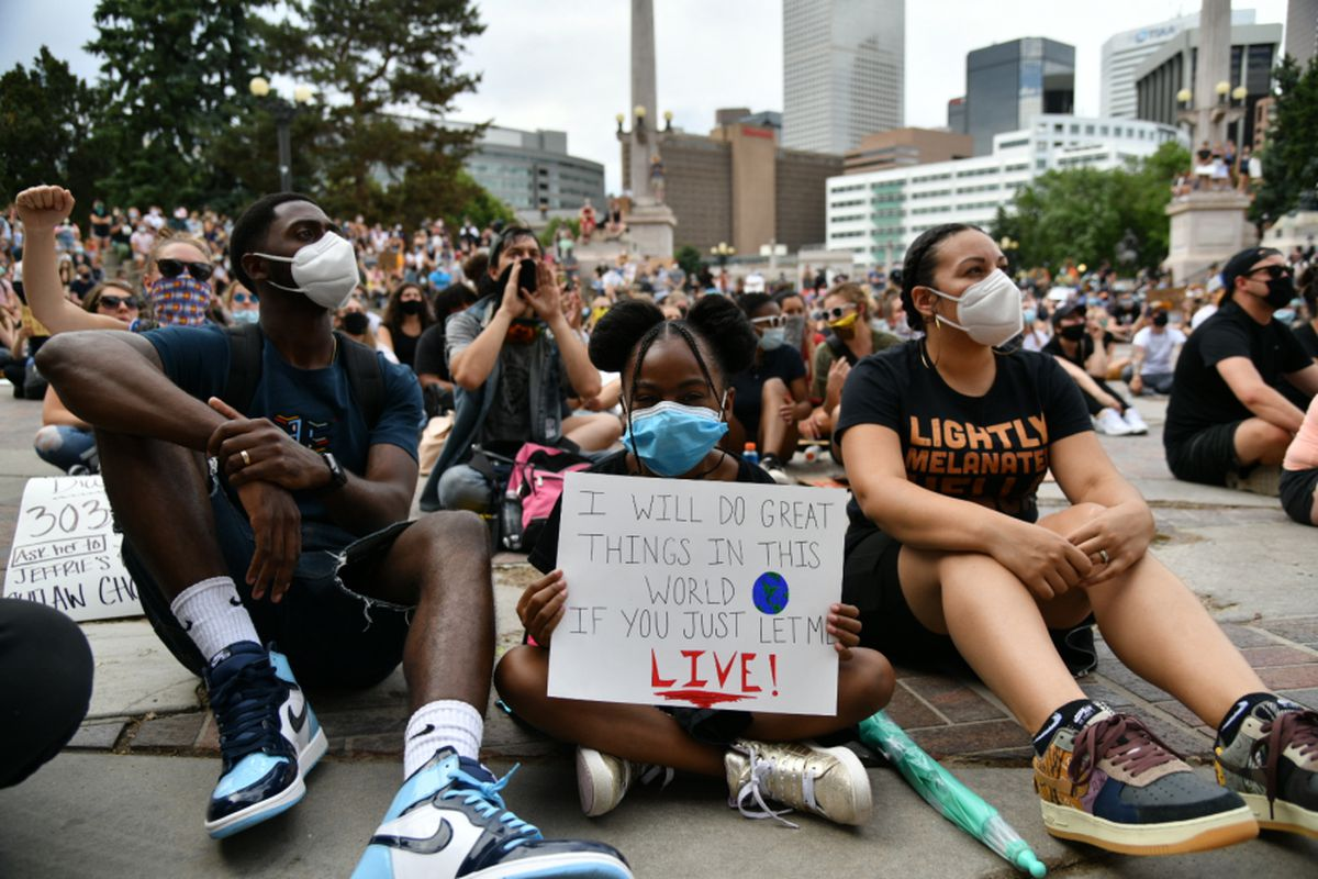 Sanaa Smith-Shabazz, 8, sits between her parents Ibn Shabazz, left, and Sidney Smith-Shabazz during a gathering at Civic Center Park in Denver on Thursday, June 4, 2020.