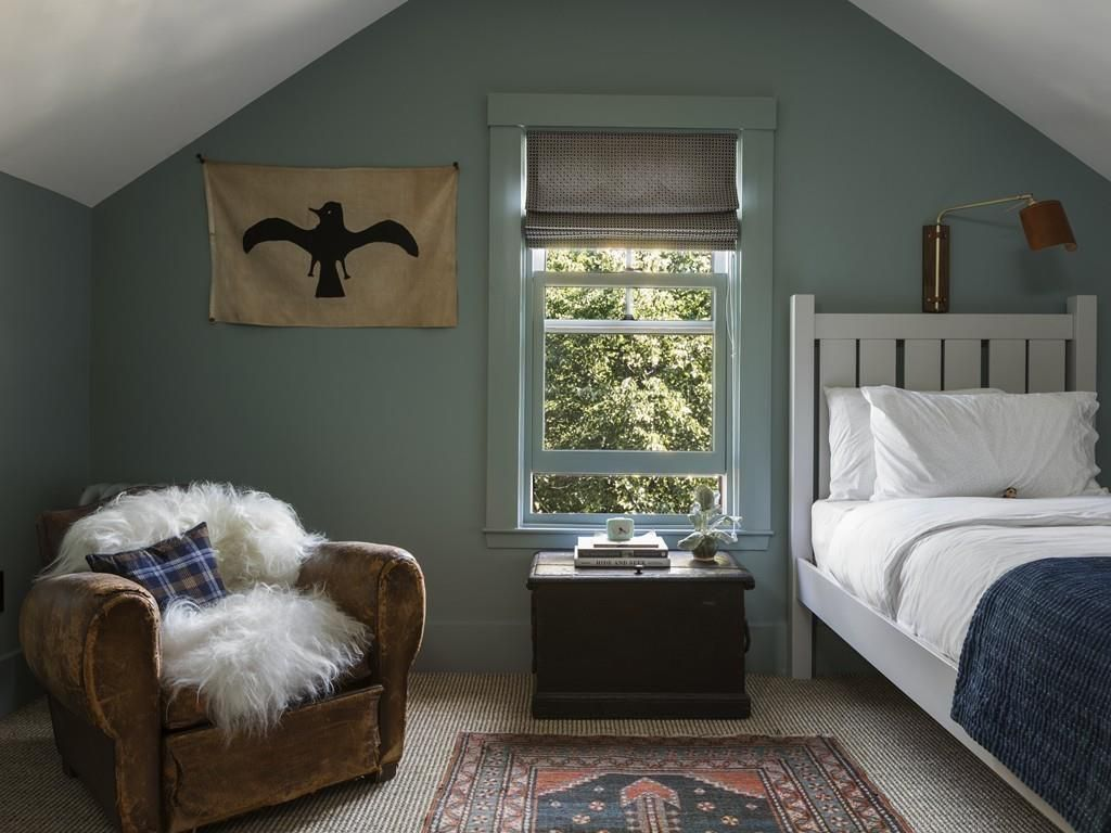 A bedroom with a triangular, peaked ceiling with a bed, a chair, a nightstand, and a window.