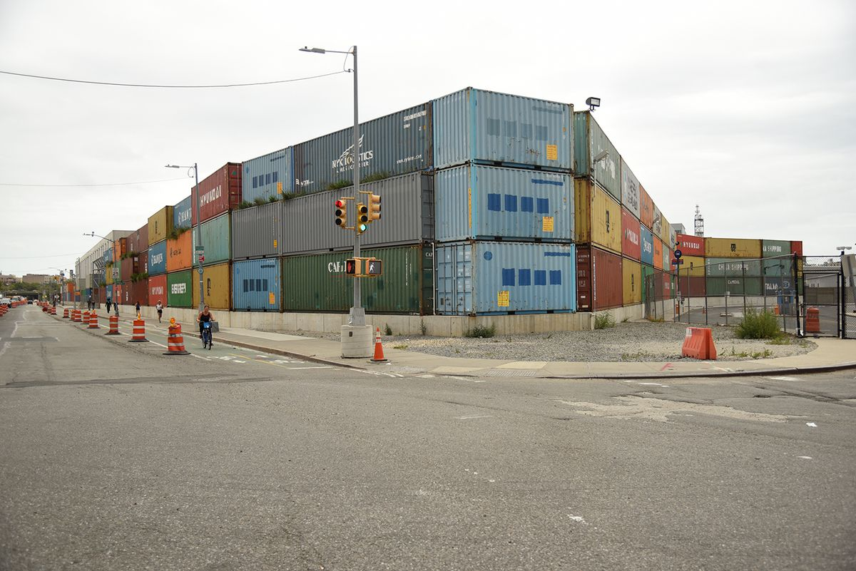 A stack of shipping containers on a street corner.