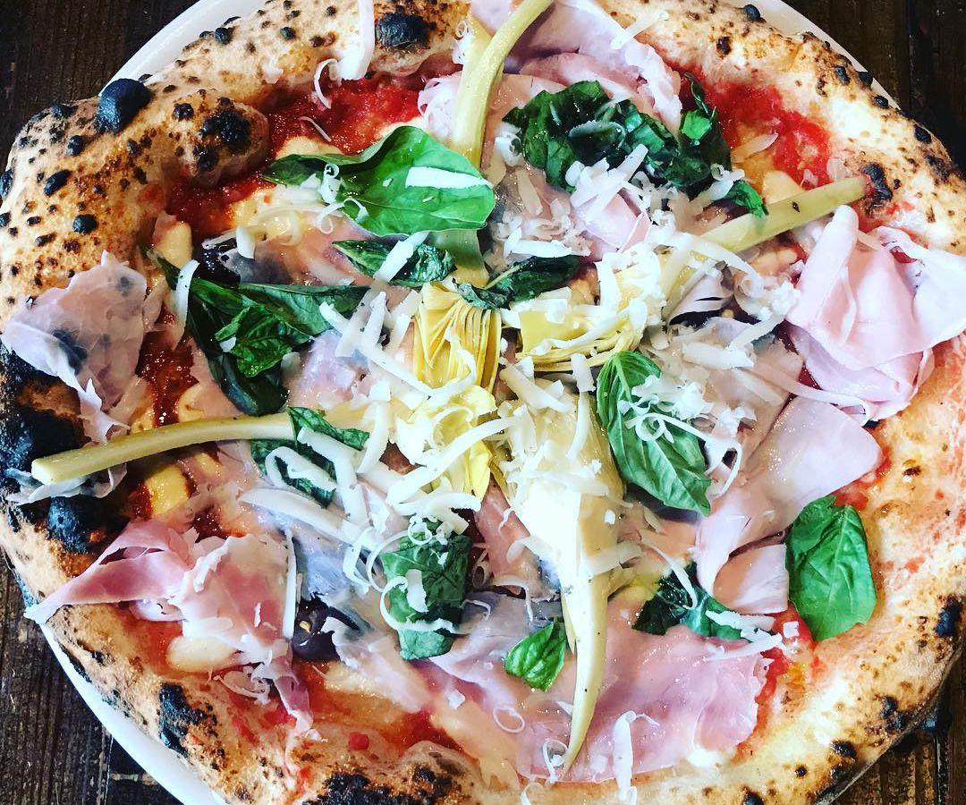 A pizza with mozzarella, Roman artichoke, fresh cotto, marinated olives, Roman shaved pecorino, garlic, and tomato sauce