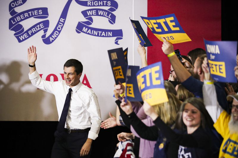 """Former South Bend, Indiana, Mayor Pete Buttigieg raises a hand in greeting while supporters wave """"Pete 2020"""" signs."""