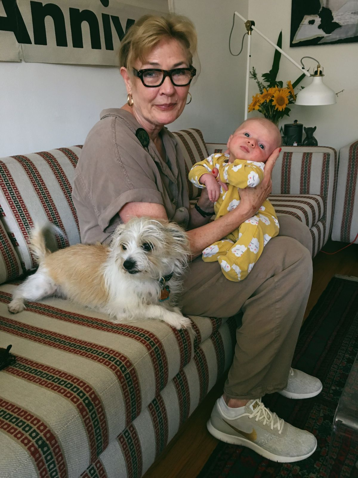 A woman in glasses holds a baby while sitting on a couch. A small white dog is sitting next to her.