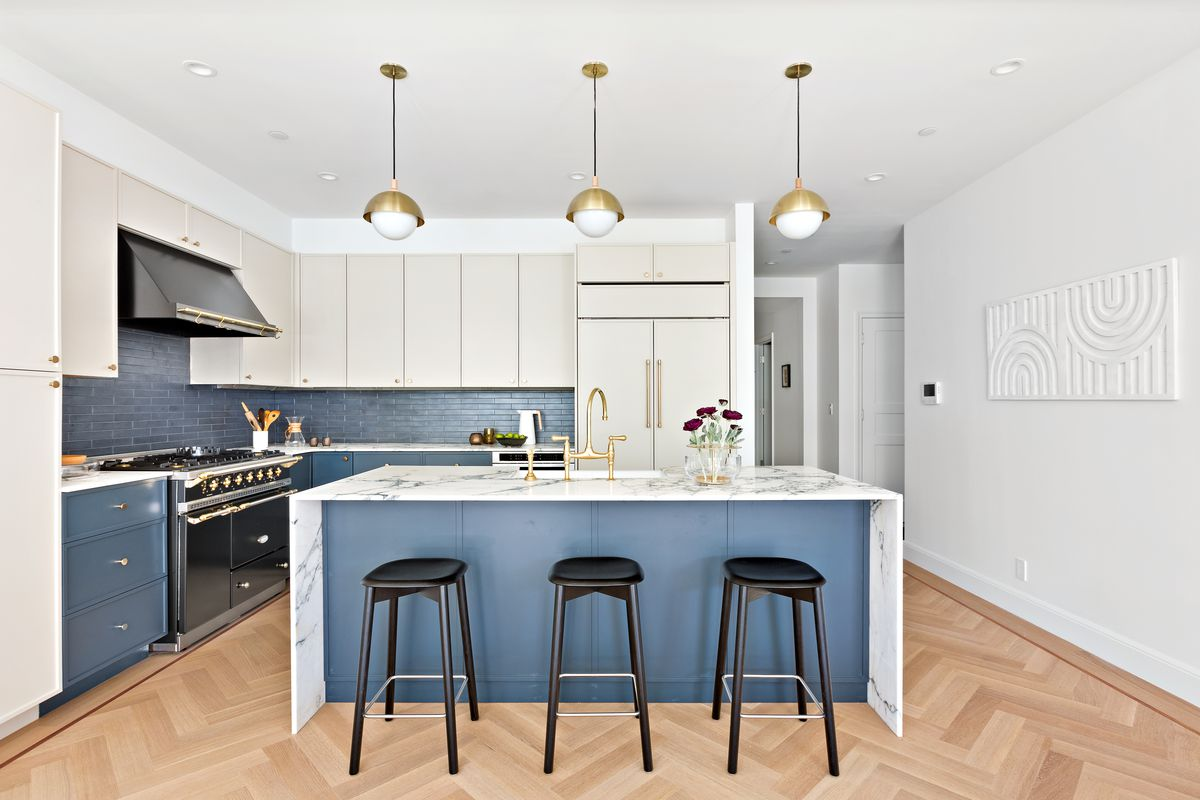 A kitchen with blue and white cabinetry and an island with three high top chairs.