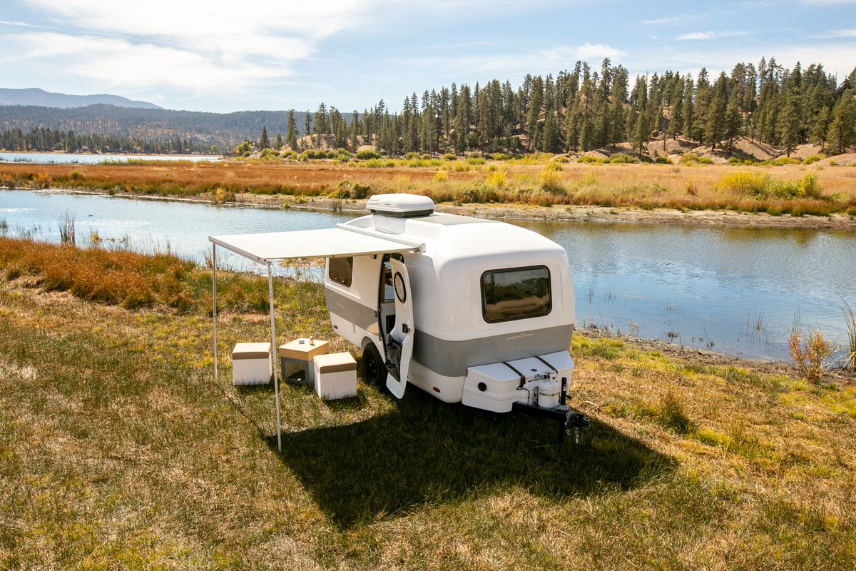 A two-toned camper sits next to a river with its door open and its awning out. Cube-like seats and a cube table sit under the awning.
