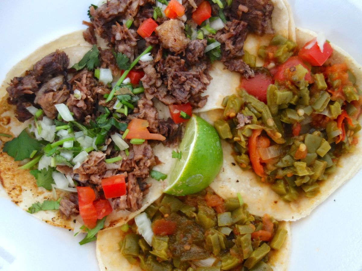 Plate of four tacos with lime