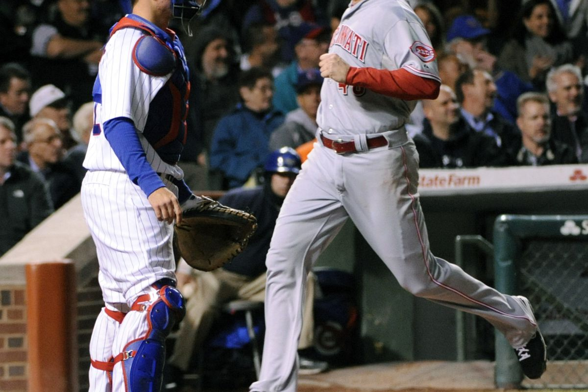 Ryan Ludwick of the Cincinnati Reds scores as Steve Clevenger of the Chicago Cubs waits for a throw at Wrigley Field in Chicago, Illinois.  (Photo by David Banks/Getty Images)