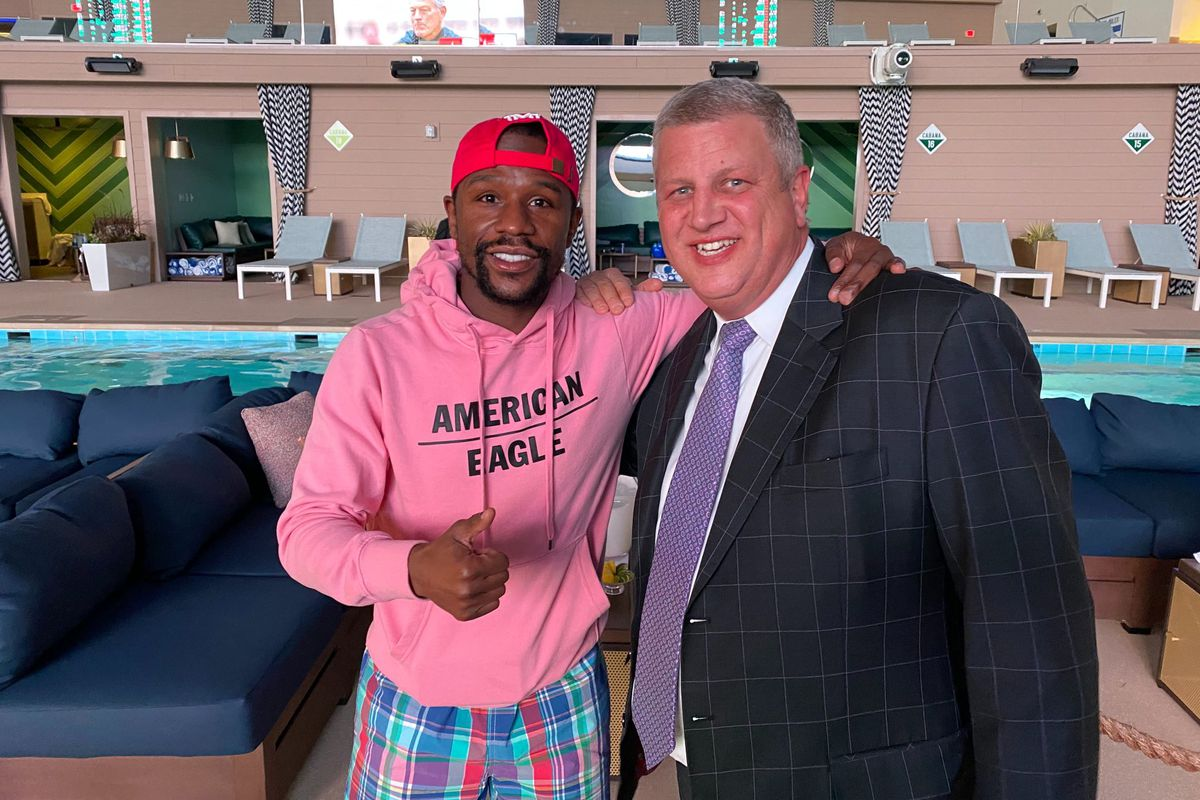 A man in a pink hoodie with a red ballcap and a man in a suit stand in front of a pool