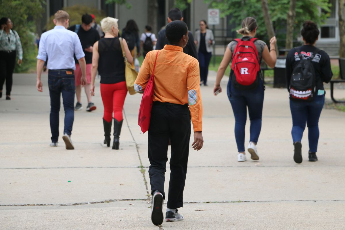 A young man wearing an orange shirt, black pants and carrying a red bag walks on a college campus behind other college students.