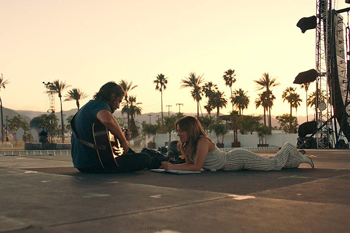 Still of Bradley Cooper and Lady Gaga sitting on the ground with a guitar in 'A Star Is Born'