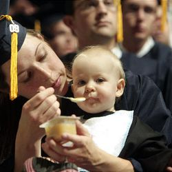 Graduate Laura Platt feeds her 11-month-old daughter, Emmalyn, during BYU's summer commencement exercises at the Marriott Center in Provo on Thursday.