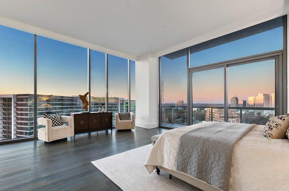 A white condo bedroom with huge windows on all sides.