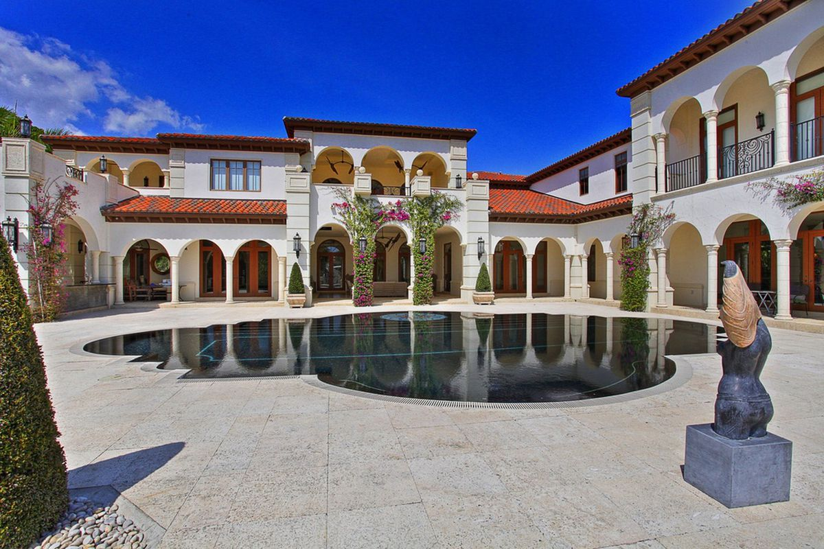 The backyard view of a stunning Mediterranean estate in Coral Gables with a sleek pool in front of it.