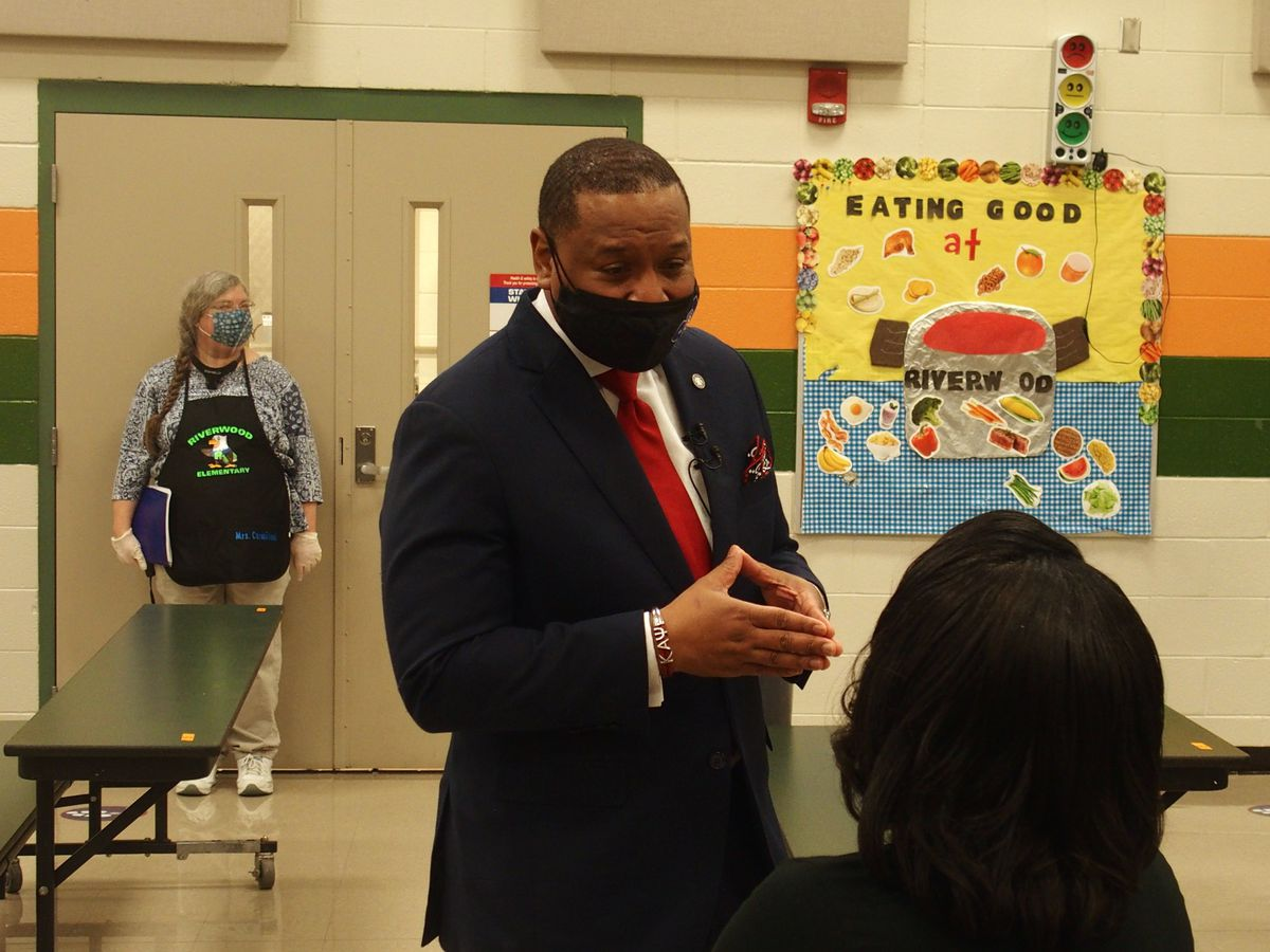 Superintendent Joris Ray speaks with a Riverwood Elementary staff member in the cafeteria with his mask on
