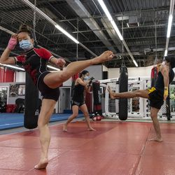 Lan Phan, left, and Jun Phan, center, follow along with Anthony Marquez owner and head coach at EFK Martial Arts, 5951 N. Clark St., during a boxing class on the first day of Illinois' Phase 4 reopening, Friday, June 26, 2020.