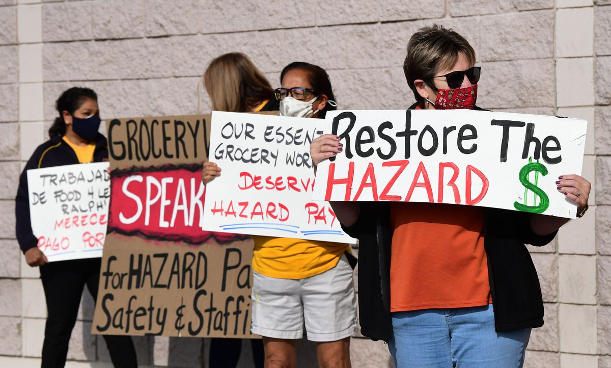 """Four people standing outside holding signs. One reads """"Restore the hazard $."""""""