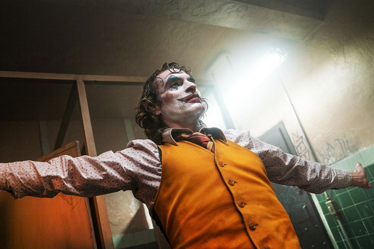 Joaquin Phoenix as the Joker spreads his arms wide.