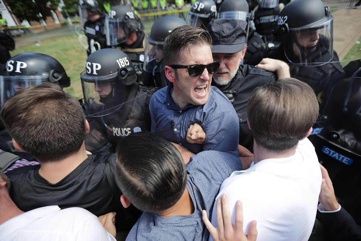"""CHARLOTTESVILLE, VA - AUGUST 12:  White nationalist Richard Spencer (C) and his supporters clash with Virginia State Police in Emancipation Park after the """"Unite the Right"""" rally was declared an unlawful gathering August 12, 2017 in Charlottesville, Virginia. Hundreds of white nationalists, neo-Nazis and members of the """"alt-right"""" clashed with anti-fascist protesters and police as they attempted to hold a rally in Emancipation Park, where a statue of Confederate General Robert E. Lee is slated to be removed. (Photo by Chip Somodevilla/Getty Images)"""
